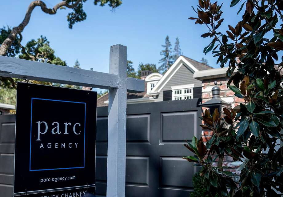 "A home at 190 Almendral Avenue is seen with a ""For sale"" sign in July in Atherton, the most expensive enclave in the Bay Area. Bay Area home prices are projected to grow slowly if at all this year. Photo: Jessica Christian / The Chronicle 2019"