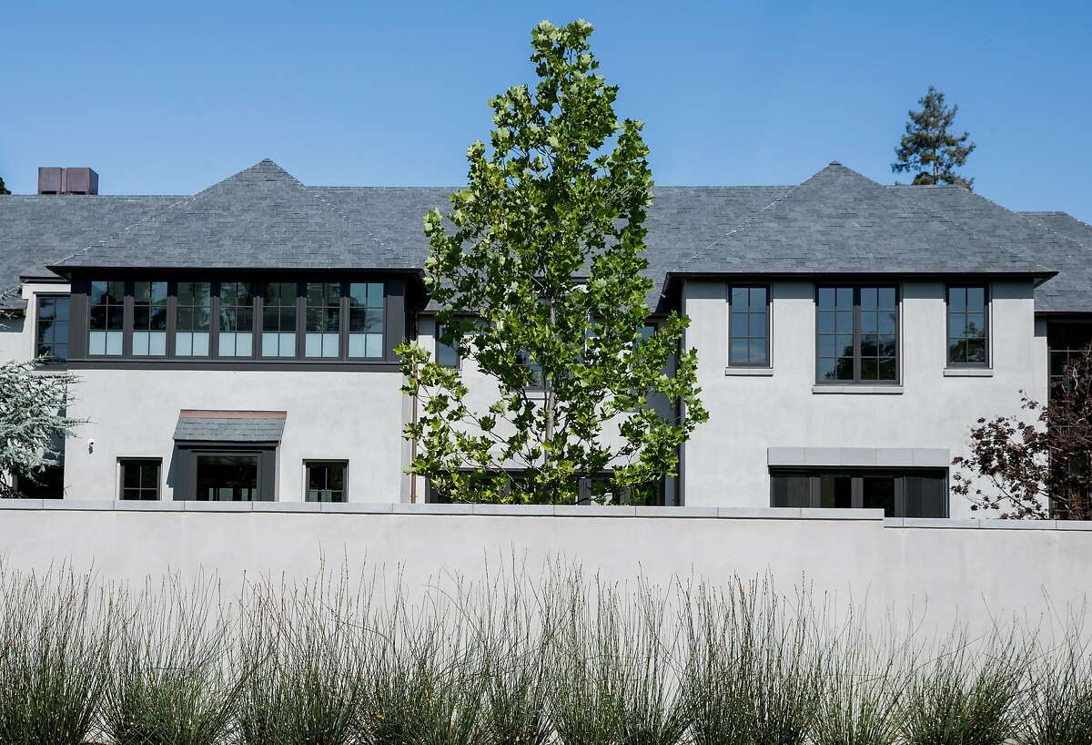 A home at 58 Tuscaloosa Avenue is seen behind a large wall in Atherton, Calif. Thursday, July 25, 2019. This property is one of the highest priced sales this year at $25 million.