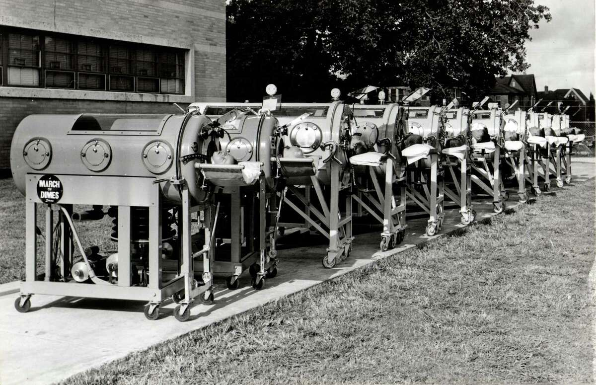 """Polio patients in iron lungare lined up in a row for photos taken July 24, 1956 for the nationwide 1957 """"March of Dimes"""" campaign staged by the National Foundation for Infantile Paralysis. All the patients, who are from the Southwestern Respiratory Center, volunteered for the photo campaign. Dry ice kept the lungs cool and comfortable for the young patients."""