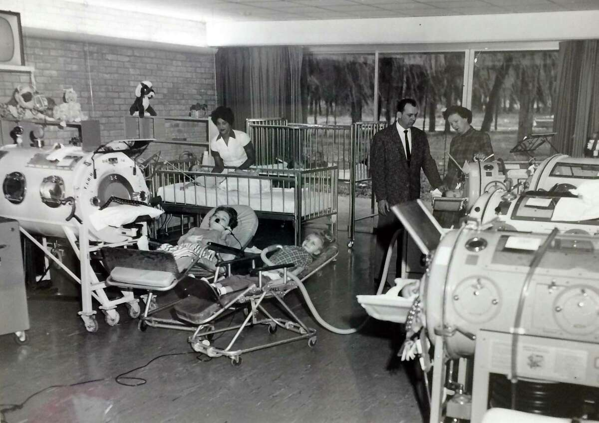 This late 1950s photo was taken in the pediatric unit at TIRR. The photo shows young polio patients receiving treatment and some patients in pneumobelts and others in tank respirators, better known as an iron lung. Polio vaccination programs have virtually eradicated new cases of poliomyelitis in the United States. Because of this, and also the development of modern ventilators and widespread use of tracheal intubation and tracheotomy, the iron lung has virtually disappeared from modern medicine.