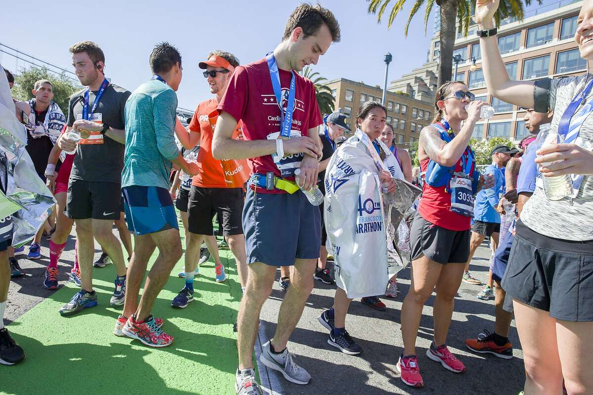Balint Gal (center) checks his running time after completing the 40th running of the San Francisco Marathon on Sunday, July 23, 2017, in San Francisco, Calif.