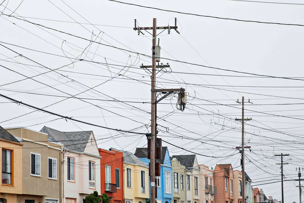 PG&E power lines cross over a view of homes and Ocean Beach seen from Rivera Street in the Sunset District of San Francisco, Calif. Friday, July 26, 2019.