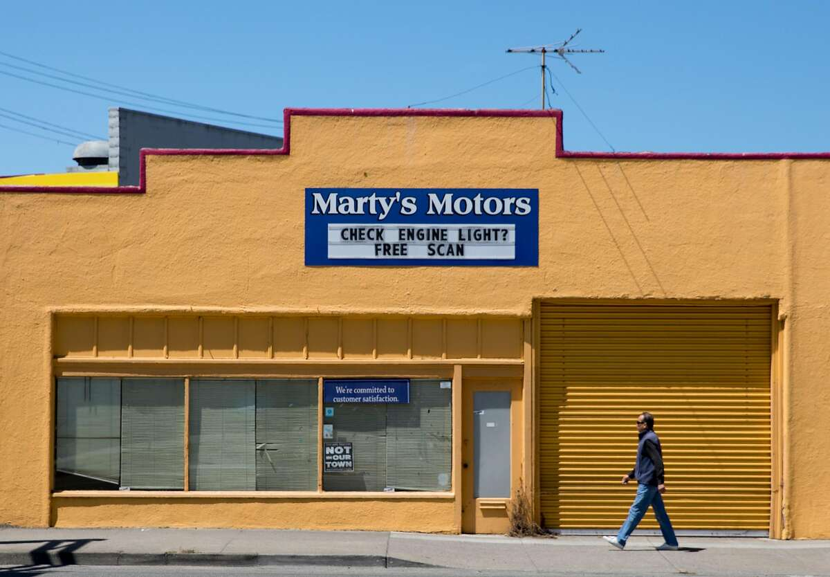 A man walks past Marty's Motors along San Pablo Avenue in El Cerrito, Calif. Tuesday, July 16, 2019.