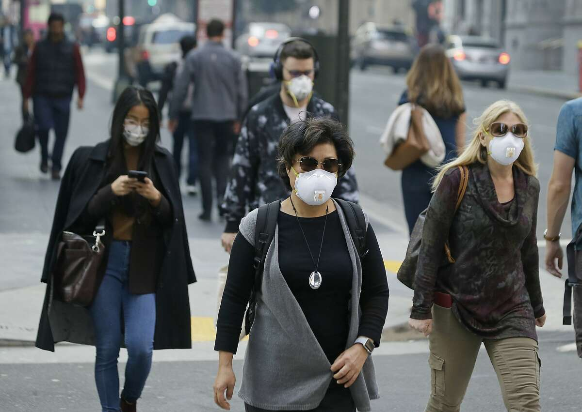 FILE - In this Nov. 9, 2018, file photo, people wear masks while walking through the Financial District in the smoke-filled air in San Francisco. Tens of millions of people in the Western US face a growing health risk due to wildfires as more intense and frequent blazes churn out greater volumes of lung-damaging smoke, according to research scientists at NASA and several major universities. (AP Photo/Eric Risberg, File)