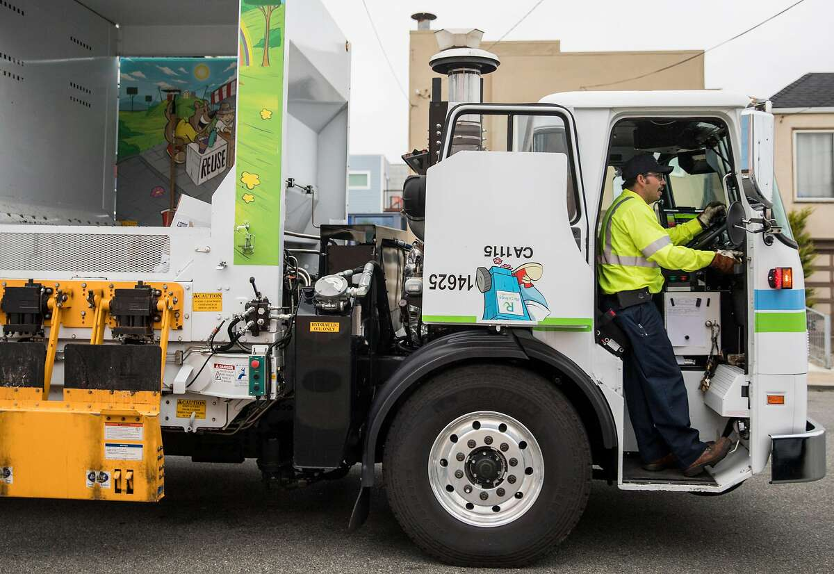 Recology collector Manuel Vera works to empty recycling bins along his route on 43rd Avenue in San Francisco, Calif. Friday, July 26, 2019.