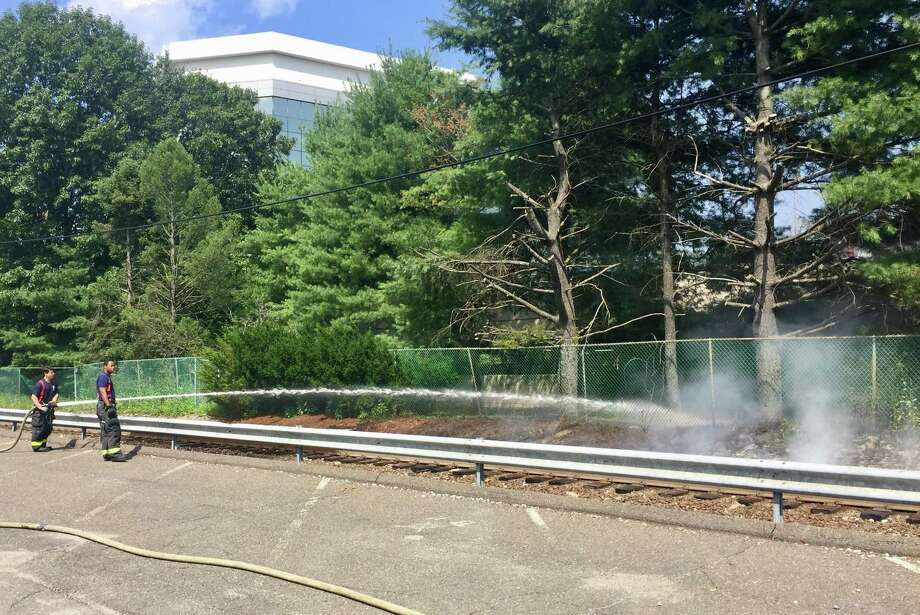 Norwalk firefighters from Engine 1 douse flames along the Danbury Line of Metro-North on Friday afternoon. The brush fire was across from 87 Glover Ave., just north of the station platform. Photo: Thane Grauel / Hearst Connecticut Media
