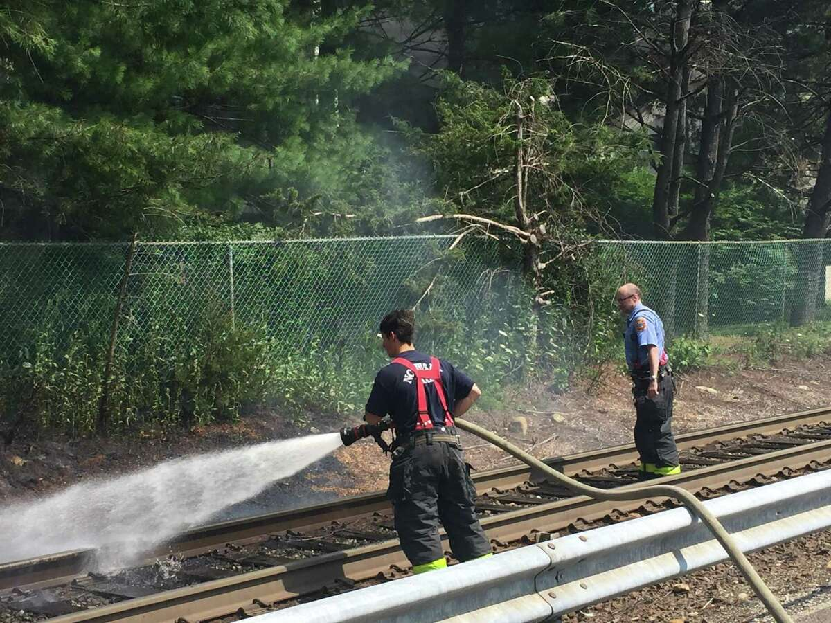 Norwalk firefighters from Engine 1 douse flames along the Danbury Line of Metro-North on Friday afternoon. The brush fire was across from 87 Glover Ave., just north of the station platform.