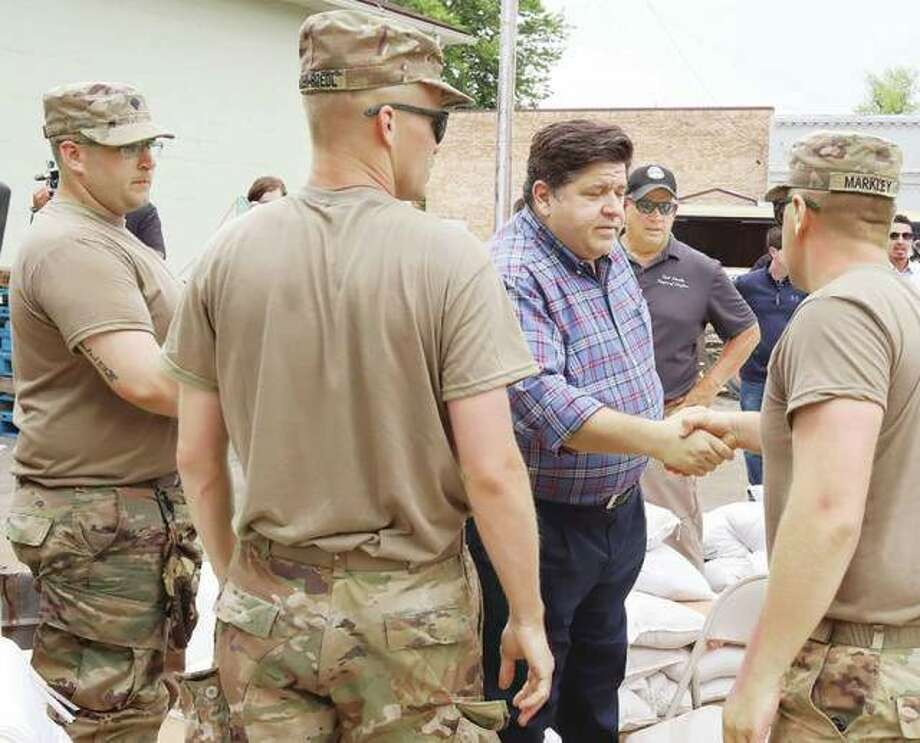 Illinois Gov. J.B. Pritzker, center, greets members of the Illinois National Guard Tuesday afternoon during a stop in Grafton to get a first hand look at flooding in the small towm last month.