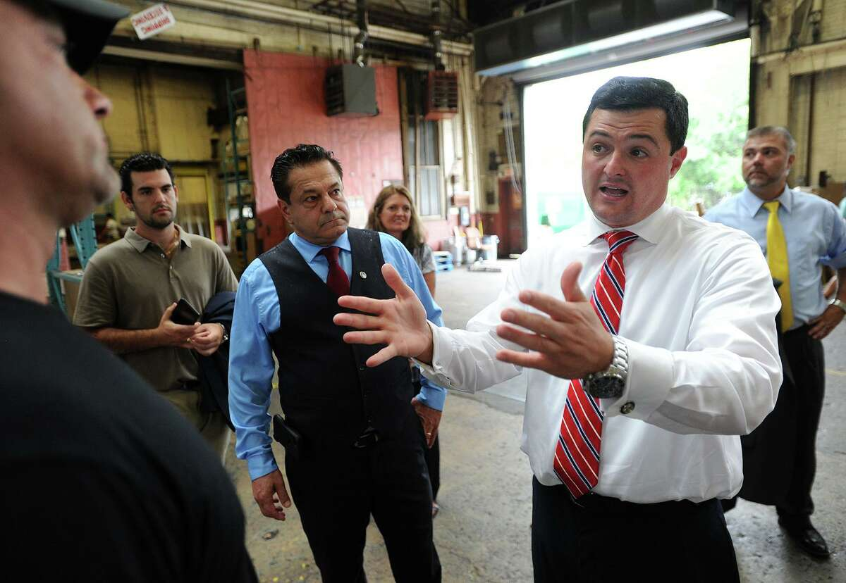 Former Trumbull First Selectman Tim Herbst, then a Republican candidate for governor, right, talks with Rugpad USA owner Karl Froehlich at his business during a campaign tour in Ansonia July 25, 2018. Accompanying Herbst is Ansonia Mayor David Cassetti.