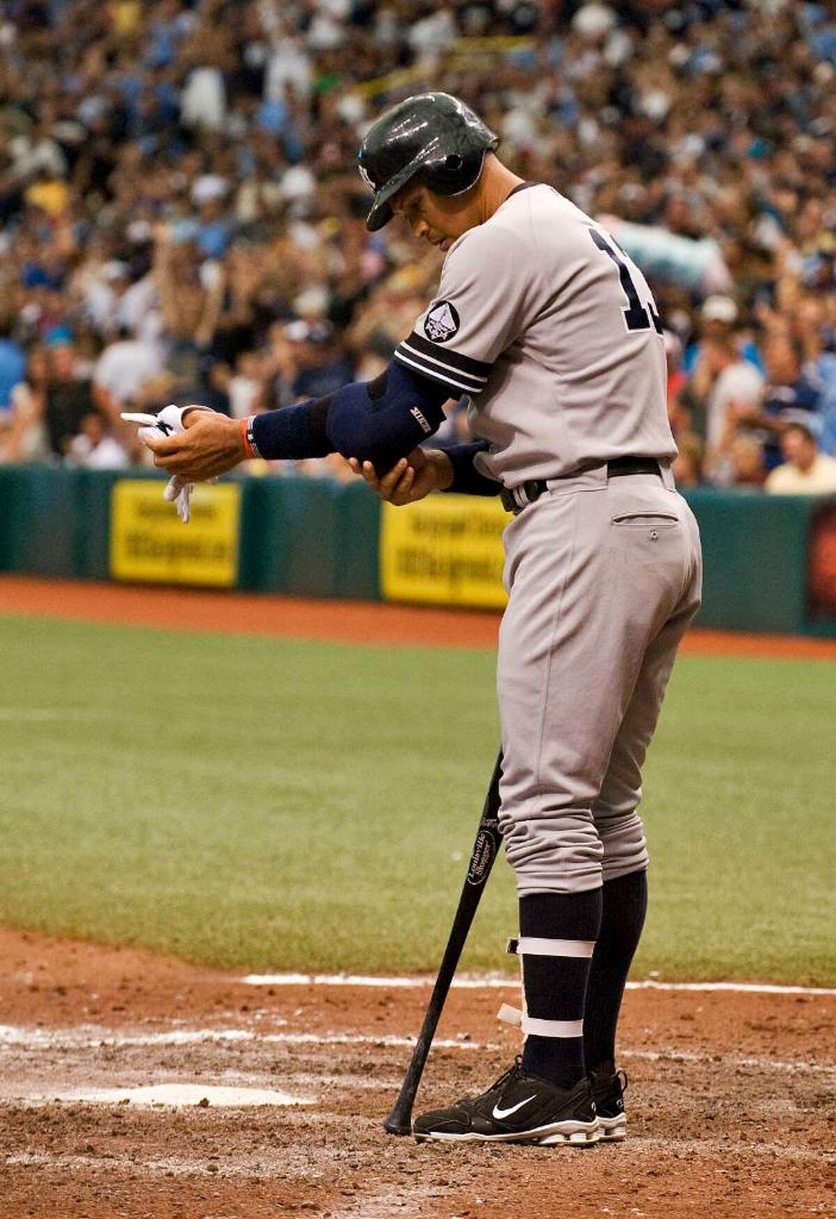 New York Yankees' Alex Rodriguez takes off his batting gear after striking out as a pinch hitter against Tampa Bay Rays pitcher James Shields to end the seventh inning of a baseball game Sunday, Aug. 1, 2010, in St. Petersburg, Fla. The Rays defeated the Yankees 3-0. (AP Photo/Steve Nesius)