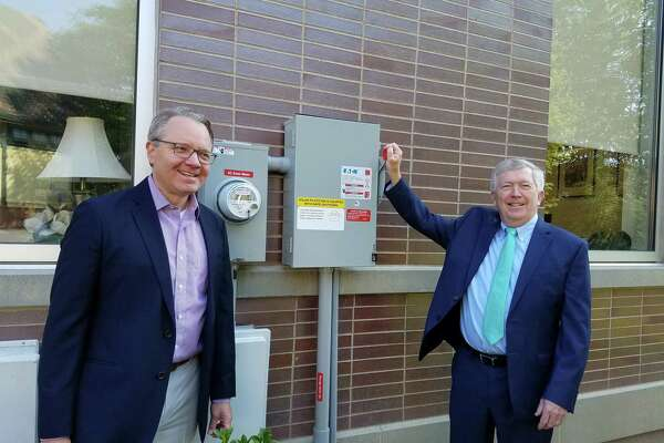 First Selectman Kevin Moynihan raised the lever to turn on the 128 solar panels on the roof of New Canaan Town Hall on July 25. Cheering him on is Mark Robbins of MHR Development, LLC