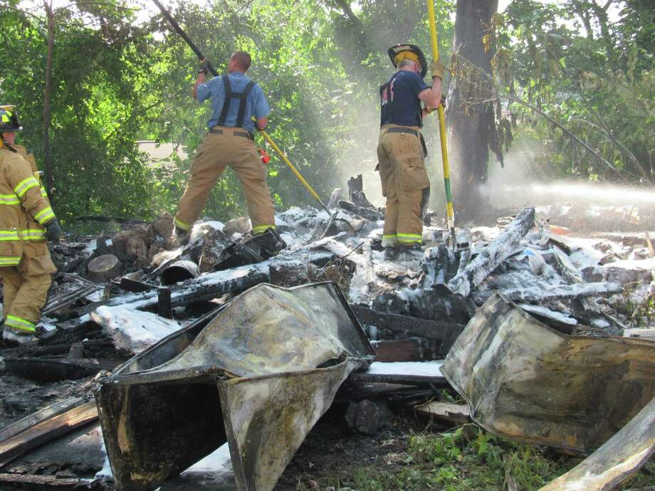 Firefighters tending a fire caused by someone using gasoline to kill bees in a torn down shed on Lawn Avenue on Thursday, July 25. Photo: Stamford Fire Department / Contributed