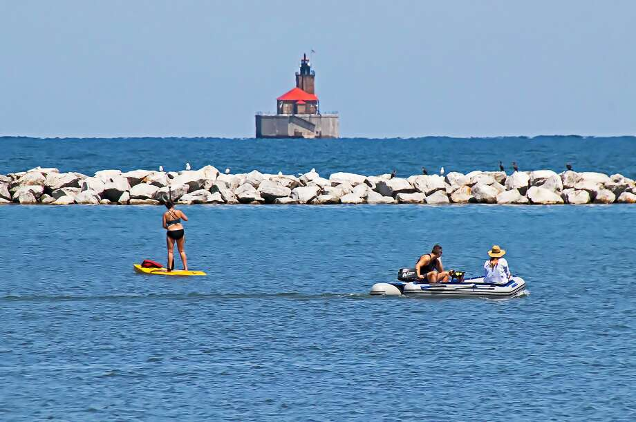 A paddle boarder and boaters were recently spotted enjoying some summer fun on the harbor in Port Austin. Photo: Bill Diller/For The Tribune