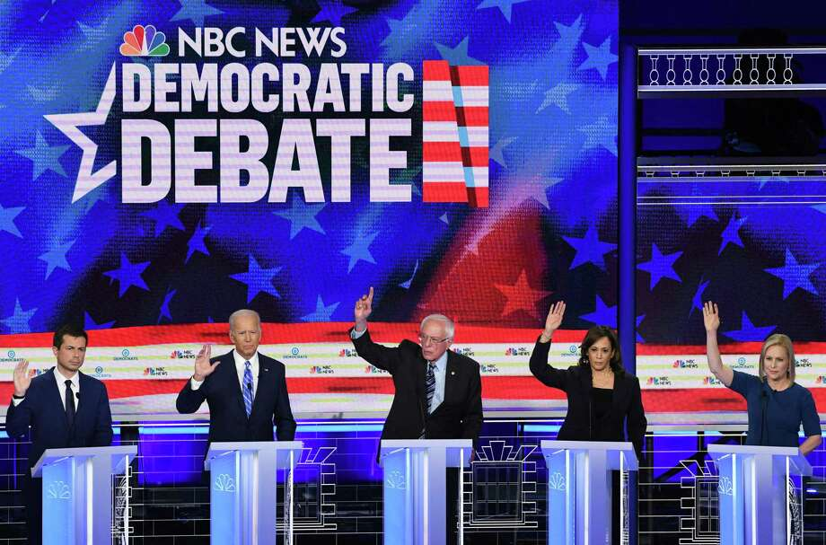 Democratic presidential hopefuls raised their hands in approval when asked if their health care for all plan would cover undocumented immigrants. Photo: SAUL LOEB /AFP /Getty Images / AFP