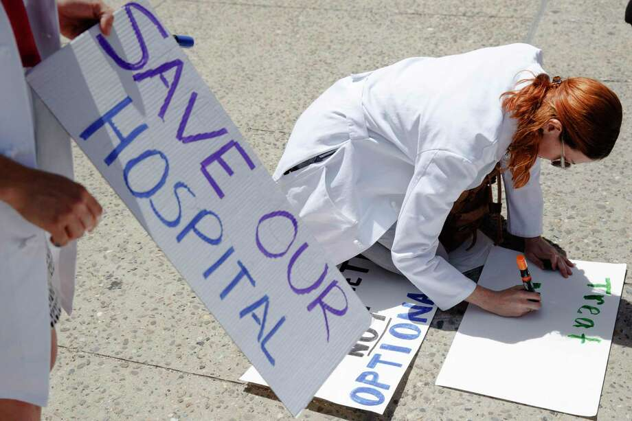 Dr. Angela Silverman makes a placard before joining a demonstration against the planned closure of Hahnemann University Hospital in Philadelphia, June 27. Financial losses incurred by drug price controls are causing hospitals to close — rural hospitals in Texas are feeling the effects as well. Photo: Matt Rourke /Associated Press / Copyright 2019 The Associated Press. All rights reserved.