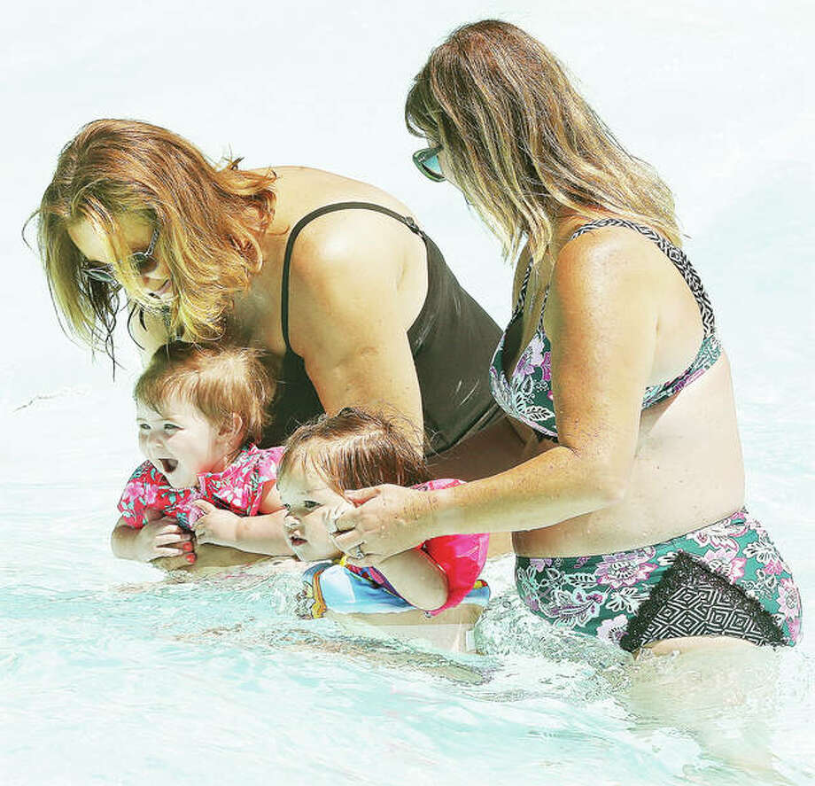 Two women entertain a couple of young children who seemed to be enjoying the water at Raging Rivers Waterpark in Grafton. Flooding forced the 28-acre park off Illinois 100, a popular attraction for the small town, to delay the start of its 30th year until July 3. The park has added hours and lengthened its season in response. Photo: John Badman|The Telegraph