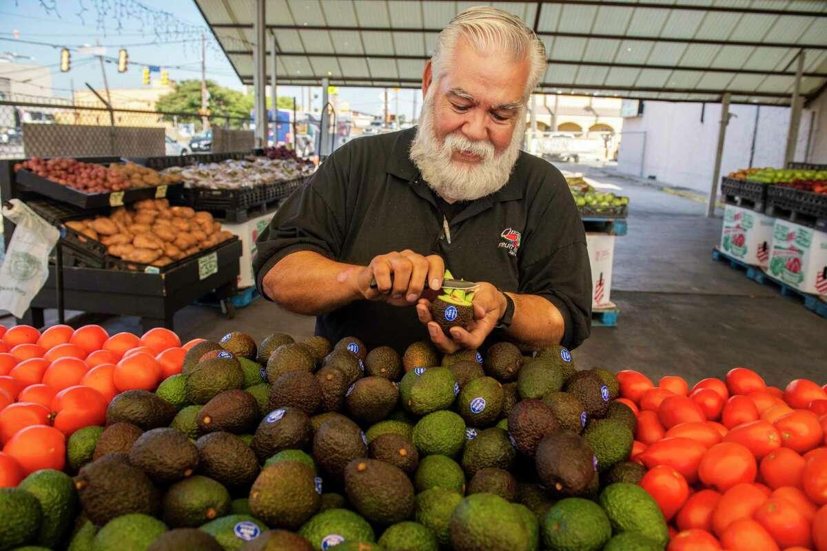 Chicho Boys Fruit Market general manager, Gilbert Weaver, sorts avocados.