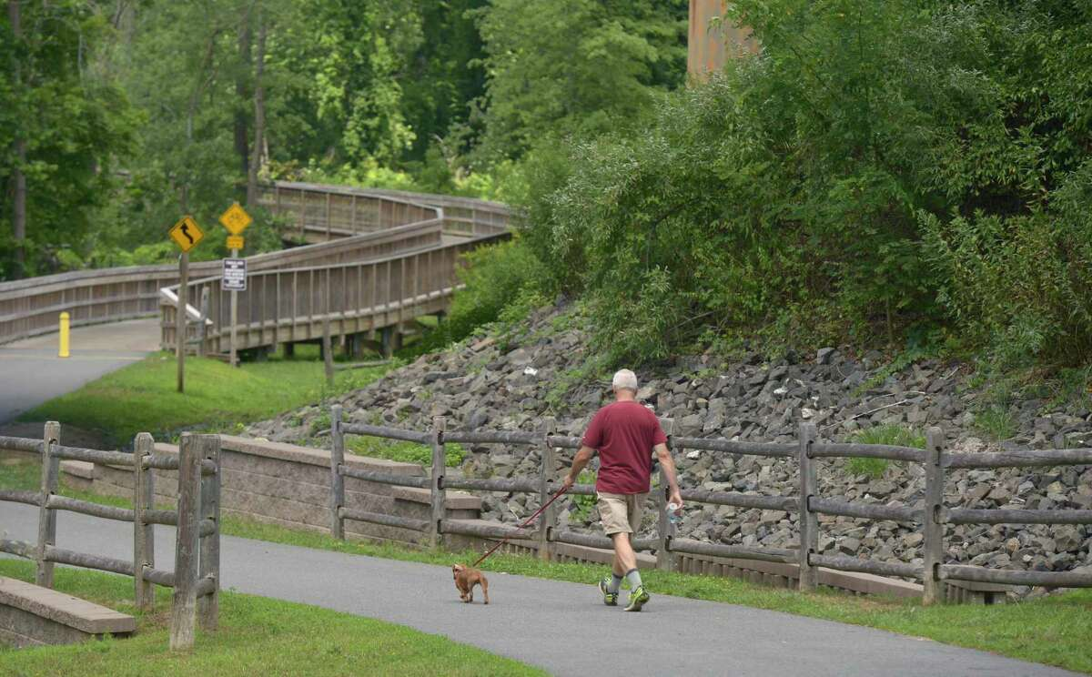 Barry Burgess, of New Milford, walks his dog Henry on Still River Greenway in Brookfield. The town is looking to extend the greenway to New Milford. Wednesday, July 24, 2019, in Brookfield, Conn.