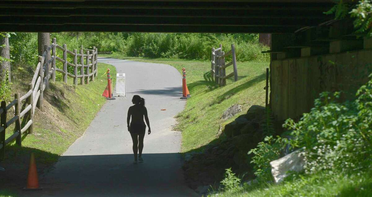 A walker passes under Route 7 while walking on the Still River Greenway in Brookfield. The town is looking to extend the greenway to New Milford. Wednesday, July 24, 2019, in Brookfield, Conn.