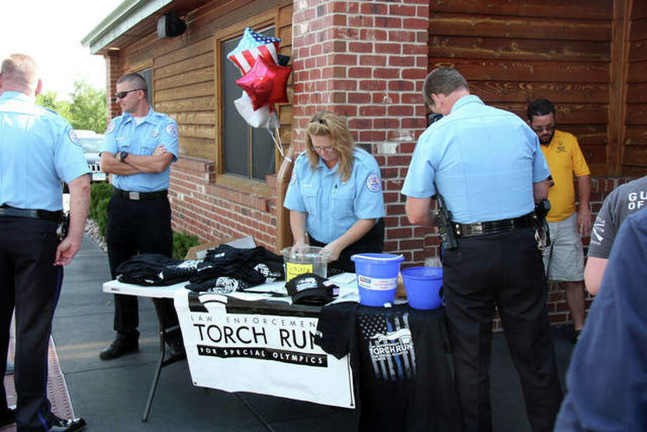 Members of the Edwardsville Police Department set up a merchandise table for Texas Roadhouse customers to purchase Special Olympics gear. The sales were part of a fundraiser Friday to benefit the charity.