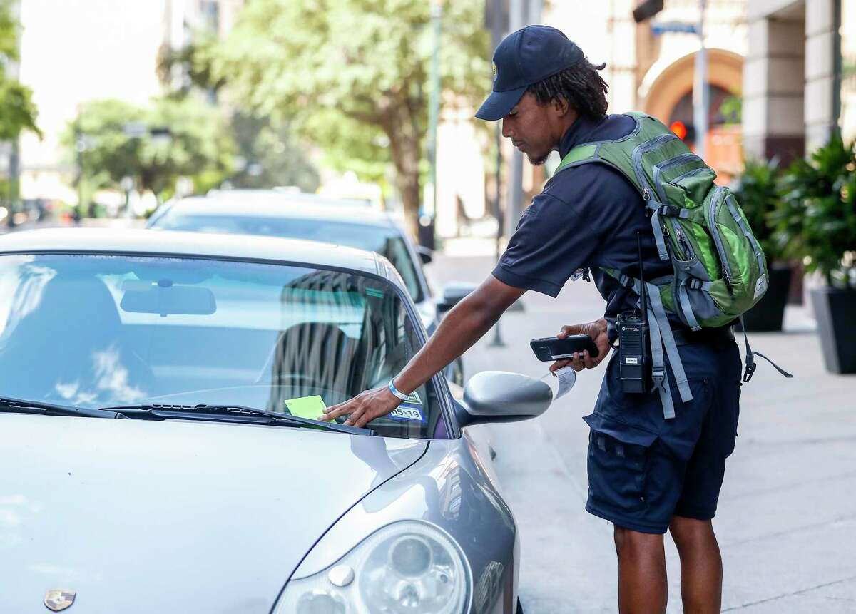 Morgan Metoyer, a City of Houston parking ticket officer, places a ticket on a car, whose driver had not paid for parking while on his route in downtown Houston, Thursday, July 18, 2019.