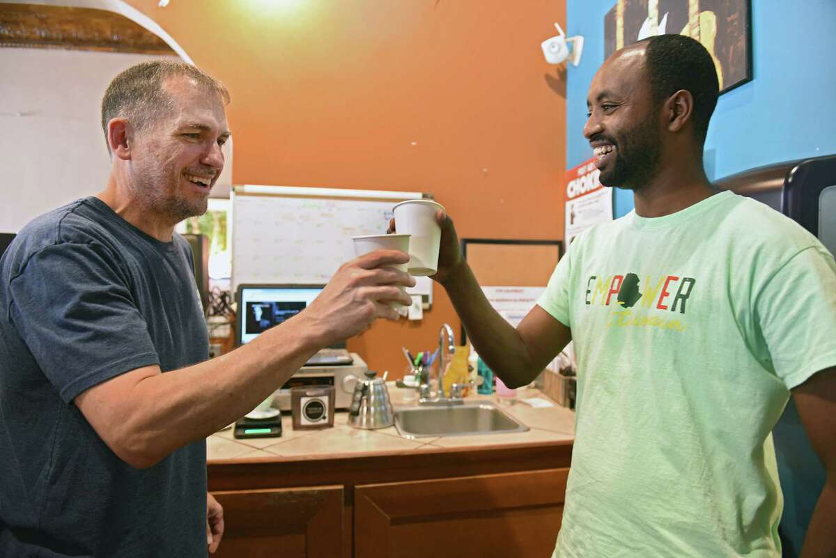 Happy Cappuccino co-owner Matt Robbins, left, makes a toast with Belayneh Woldemariam of Ethiopia who was sampling various coffees as Empower Ethiopian hosts a conversation and cultural exchange at Happy Cappuccino on Friday, July 26, 2019 in Schenectady, N.Y. The shop, which is located on Jay St., donated $1 from every coffee purchased during the fundraiser to Empower Ethopia. (Lori Van Buren/Times Union)