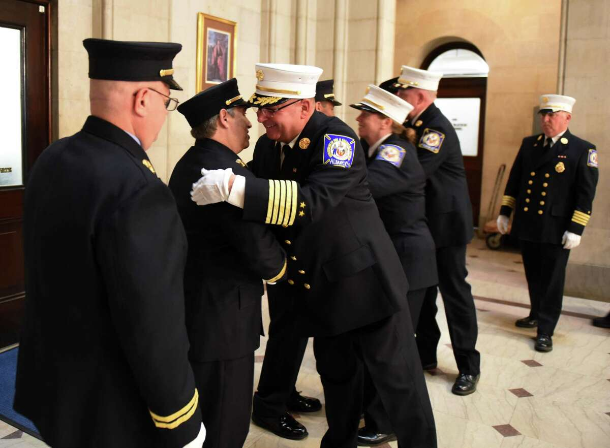 Albany Fire Department Chief Joseph Gregory congratulates Capt. Wayne Brennan, and other promotees, during the conclusion of a promotion ceremony on Friday, July 26, 2019, at City Hall in Albany, N.Y. (Will Waldron/Times Union)