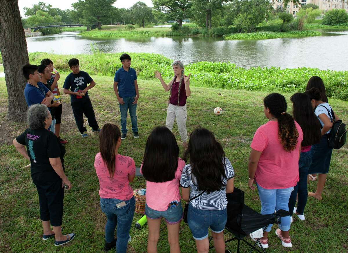 Kamala Platt talks with students in the Summer Youth Leadership Program of Fuerza Unida about nature during a visit to Elmendorf Lake.
