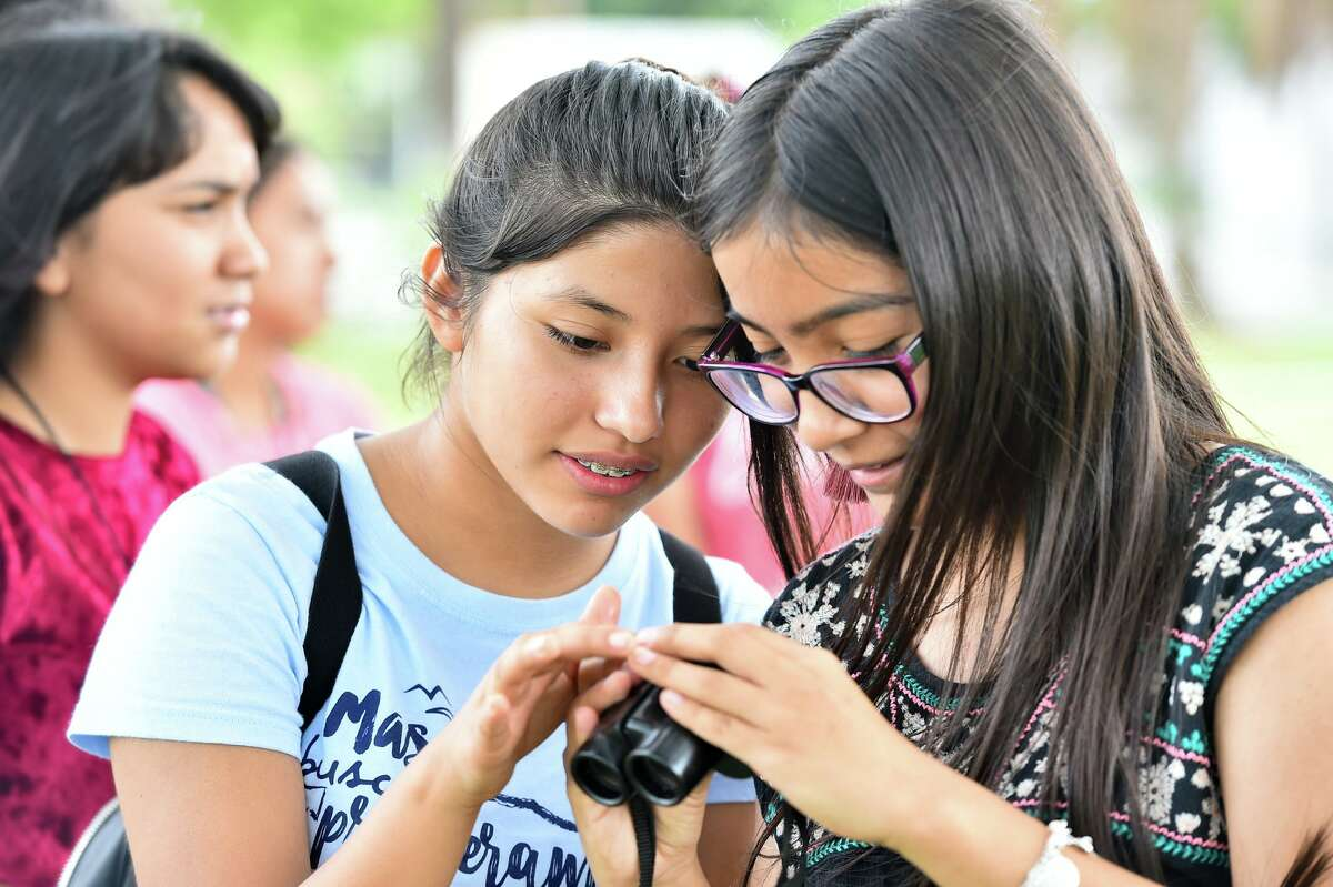 Leslye Aguilar, left, and Jazmin Flores inspect a pair of binoculars. The program is in its 29th year.