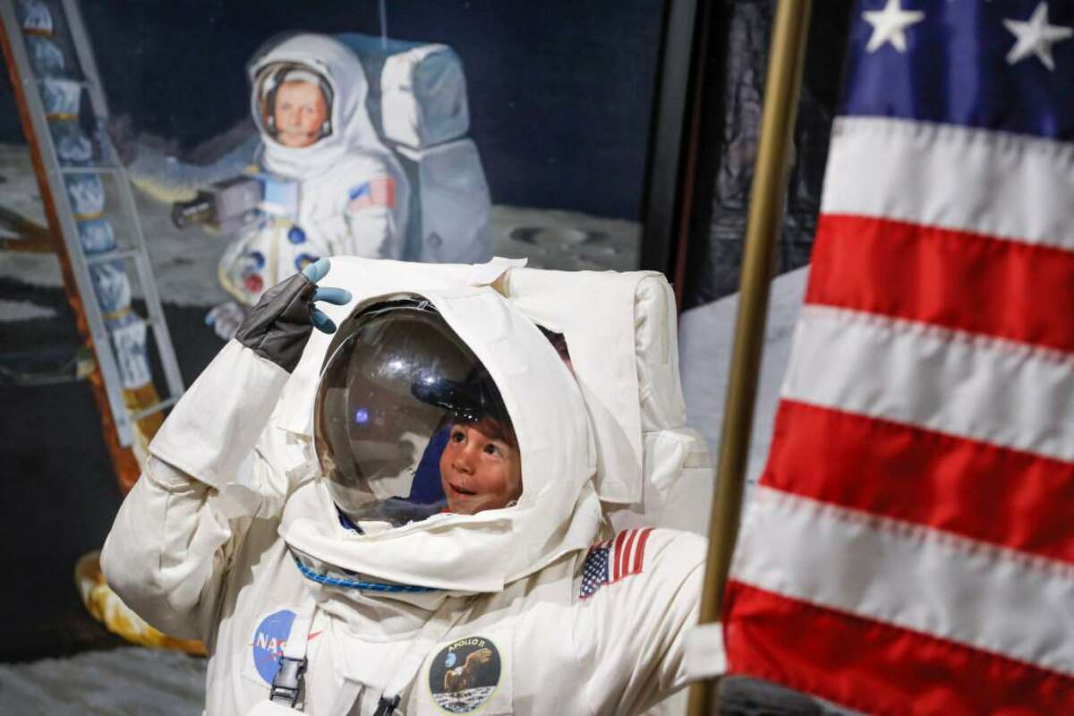 Visitors pose for photos beside a portrait of Neil Armstrong at the Armstrong Air & Space Museum this month in Wapakoneta, Ohio.