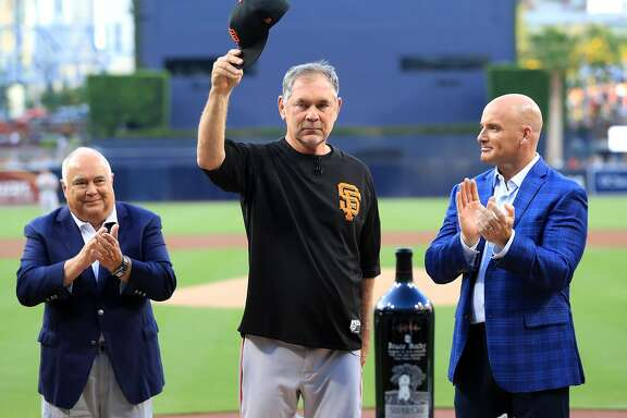 SAN DIEGO, CALIFORNIA - JULY 26: Executive chairman of the ownership group of the San Diego Padres Ron Fowler, and former MLB player Mark Sweeney congratulate manager Bruce Bochy of the San Francisco Giants as he acknowledges the crowd regarding his upcoming retirement during a pregame ceremony prior to a game between the San Diego Padres and the San Francisco Giants at PETCO Park on July 26, 2019 in San Diego, California. (Photo by Sean M. Haffey/Getty Images)