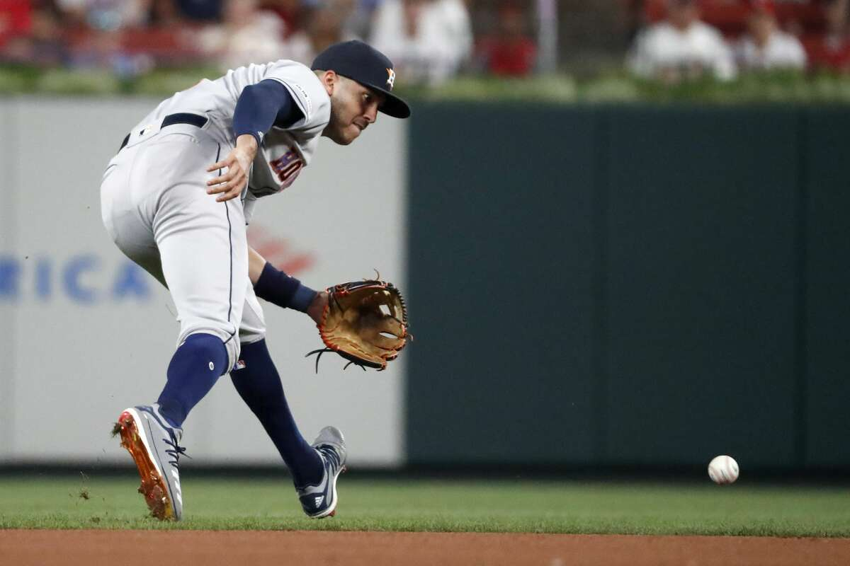 Houston Astros shortstop Carlos Correa handles a grounder by St. Louis Cardinals' Jose Martinez during the sixth inning of a baseball game Friday, July 26, 2019, in St. Louis. (AP Photo/Jeff Roberson)