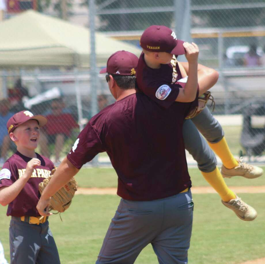 Deer Park Mustang All-Star Manager Ryan Kight lifts Teagan Land high off the ground as he celebrates a big defensive play that prevented PYBSA from taking the lead in the third inning Friday.Looking on is Aiden Gorom. By the luck of the seeding, the two teams play again on Saturday at 2. Photo: Robert Avery