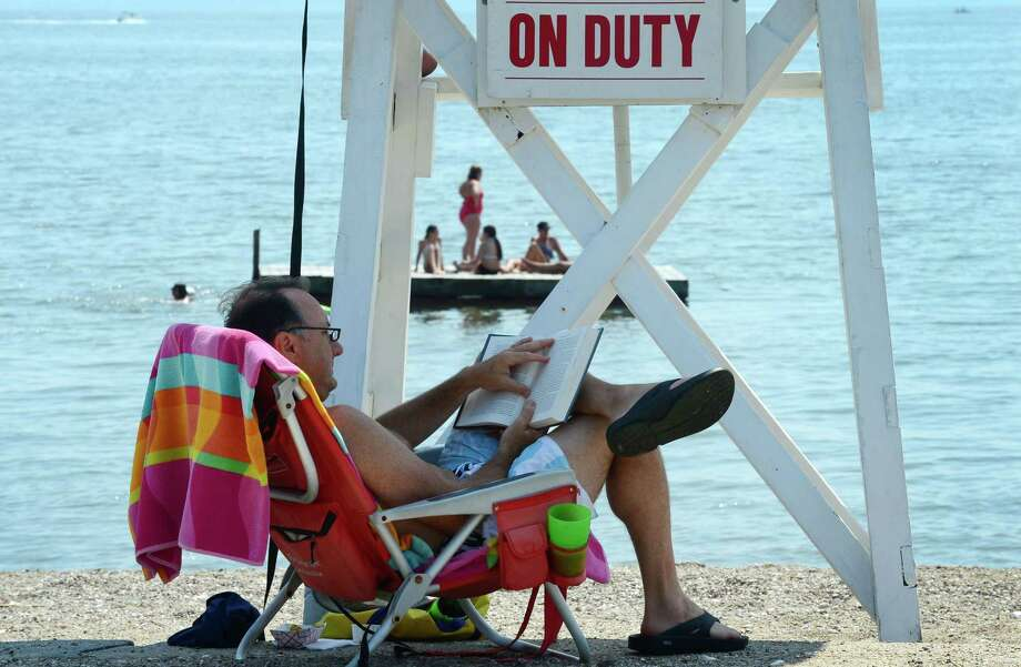 Rowayton resident Barry Fitzsimmons reads in the shade of a lifeguard stand at Bailey Beach Friday, July 26, 2019, in Norwalk, Conn. Photo: Erik Trautmann / Hearst Connecticut Media / Norwalk Hour
