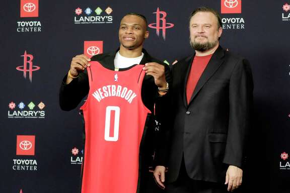 Russell Westbrook poses with his jersey with Rockets General Manager Daryl Morey during a press conference introducing him at the Toyota Center on Friday, July 26, 2019 in Houston.