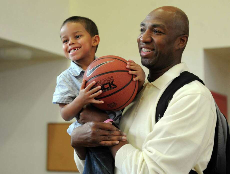 Vin Baker poses for a photo with Christopher Johnson, 4, as he works with the Housing Authority and the Bridgeport Police Department at their summer sports clinic and mentoring program in June 2011. Photo: Lindsay Niegelberg / Hearst Connecticut Media / Connecticut Post