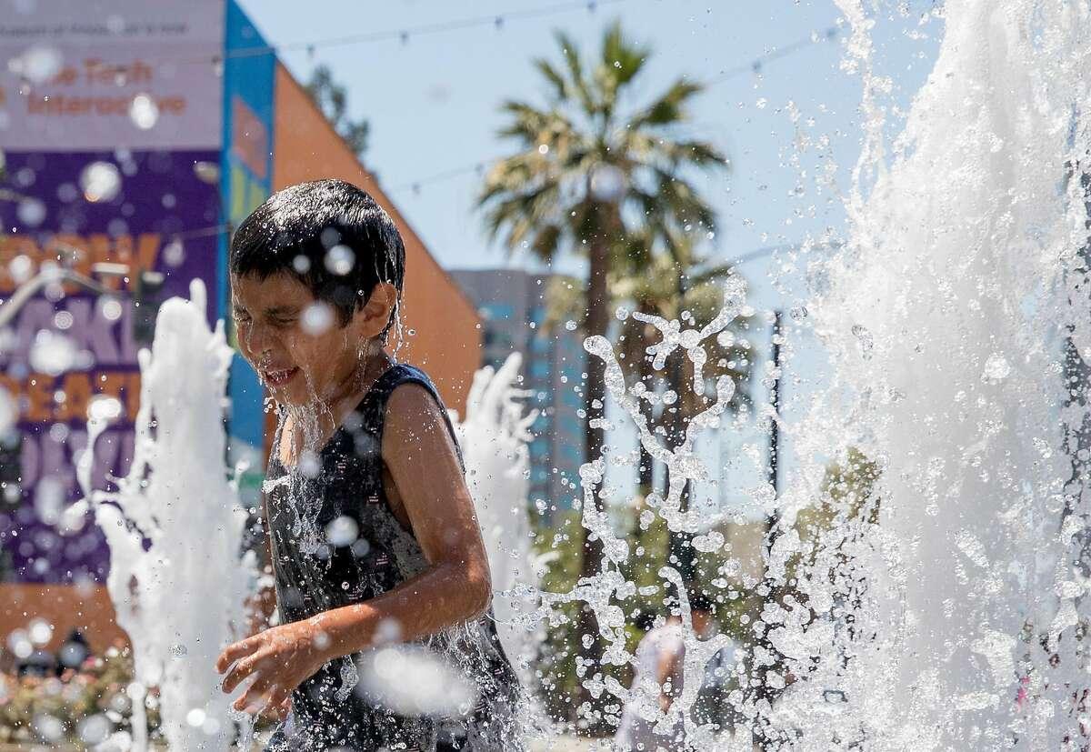 Andrew Silva, 6, runs through the fountain at Plaza de Cesar Chavez in downtown San Jose, Calif. Saturday, July 27, 2019.