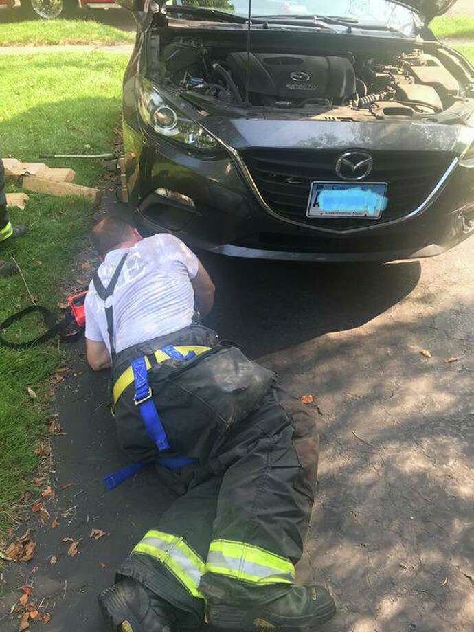 Firefighters work to get a woodchuck out of a vehicle in Hamden, Conn., on July 28, 2019. Edits to the license plate made by fire officials, not Hearst Connecticut Media. Photo: Contributed Photo / Hamden Fire Department