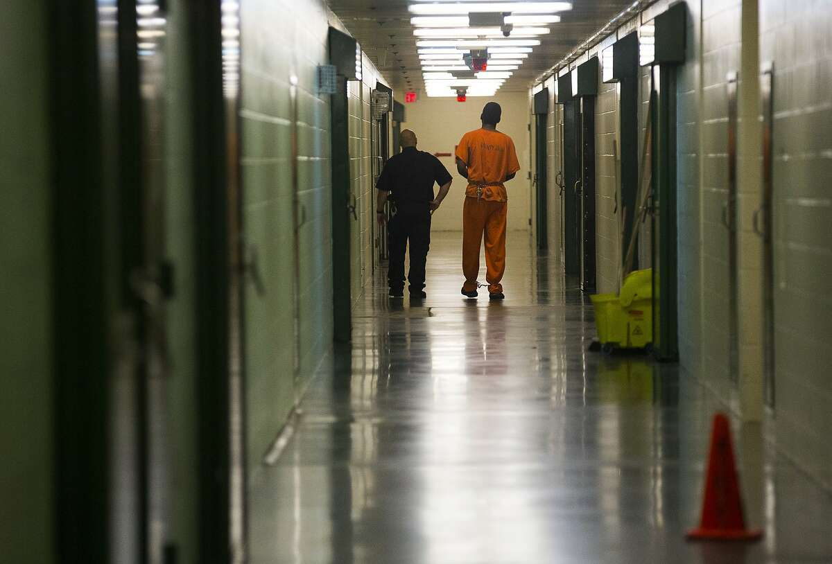 An inmate is escorted in a hallway in the Harris County jail, Thursday, March 29, 2018, in Houston.