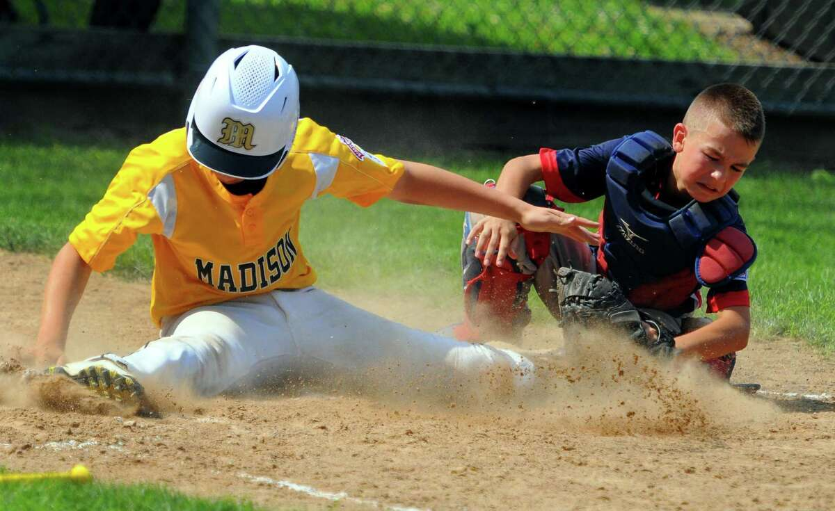 Madison's Will Pattla (35) reaches home plate as Brooklyn-Pomfret catcher Caleb Simonean (15) misses the tag during little league baseball action in Willimantic, Conn., on Saturday July 27, 2019.