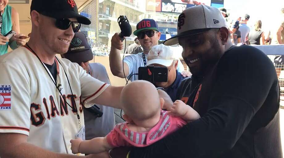 Chris Rice hands Giants second baseman Pablo Sandoval his 5-month-old daughter, Roya, in the dugout before Saturday's game against the Padres at Petco Park in San Diego. Rice's bare-handed catch of Sandoval's game-winning home run Friday night while holding Roya became an instant sensation. Photo: John Shea / San Francisco Chronicle