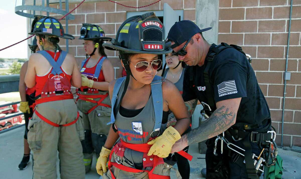 Annayelli Saldivar,14, gets hooked up by Chris Young before rapppelling. A special San Antonio Fire Department camp will give girls 14-18 hands-on experience at the SA Fire Academy to encourage a career in firefighting.on Saturday, July 27, 2019.