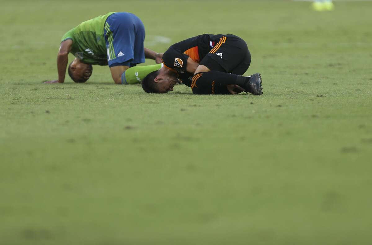 Seattle Sounders midfielder Jordy Delem (21) and Houston Dynamo midfielder Memo Rodríguez (8) both fall onto the ground after a play during the first half of the MLS game at BBVA Stadium on Saturday, July 27, 2019, in Houston.