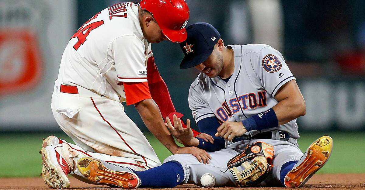 ST. LOUIS, MO - JULY 27: Yairo Munoz #34 of the St. Louis Cardinals checks on Carlos Correa #1 of the Houston Astros as Correa injured his arm while making an out against Munoz during the eighth inning at Busch Stadium on July 27, 2019 in St. Louis, Missouri. (Photo by Scott Kane/Getty Images)