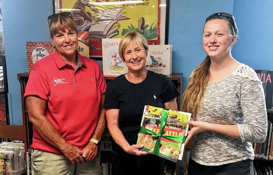 Pike-Scott Farm Bureau board member Corinna Mountain (left) and PSFB agriculture literacy coordinator Rachel Smith (right) present children's librarian Beth Stark of Pittsfield Public Library with agriculture-themed books. Photo: Photo Provided