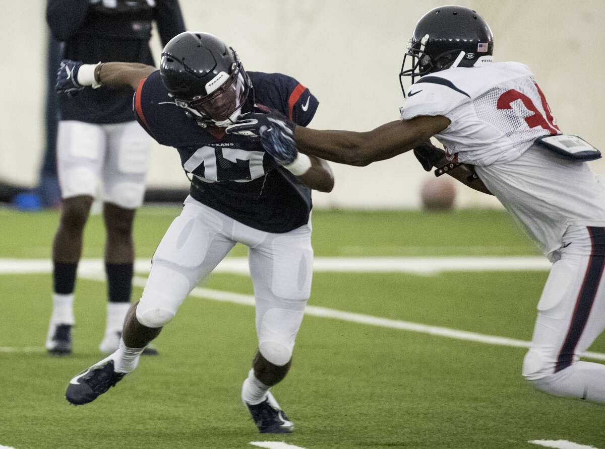 Houston Texans defensive back Austin Exford (47) rushes the passer against running back Taiwan Jones (34) during training camp at the Methodist Training Center on Sunday, July 28, 2019, in Houston.