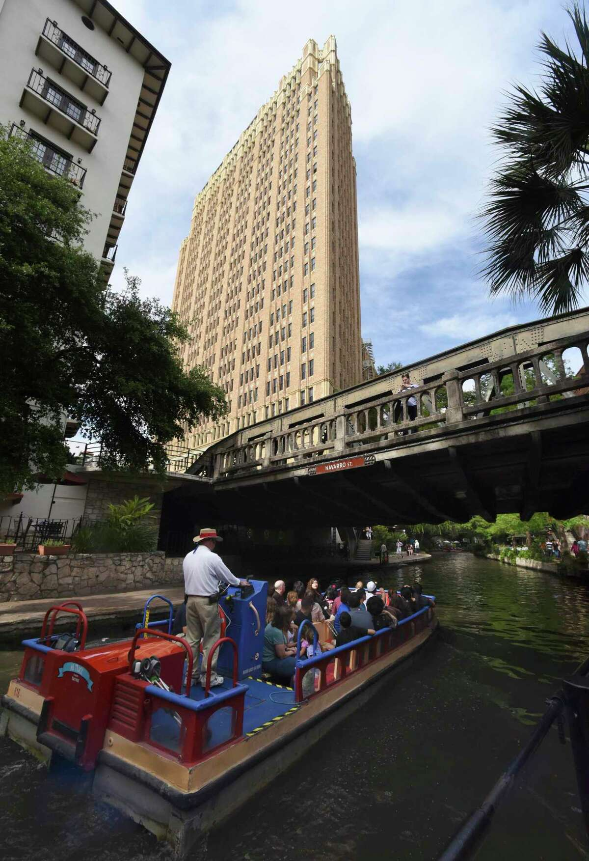 Nix Medical Center looms over a barge on the San Antonio River at the Navarro Street bridge in this 2015 photo.