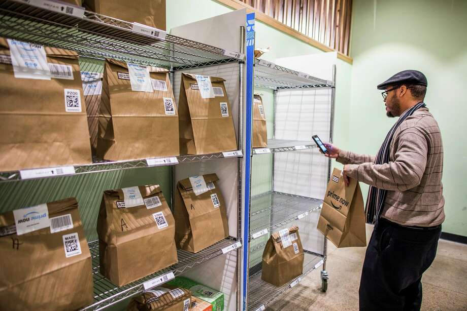 Charlton Holmes shelves groceries for two-hour delivery at the Whole Foods flagship store in Austin, Tex., last year. Amazon is now quietly exploring an ambitious new chain built for in-store shopping as well as pickup and delivery. Photo: Drew Anthony Smith For The New York Times