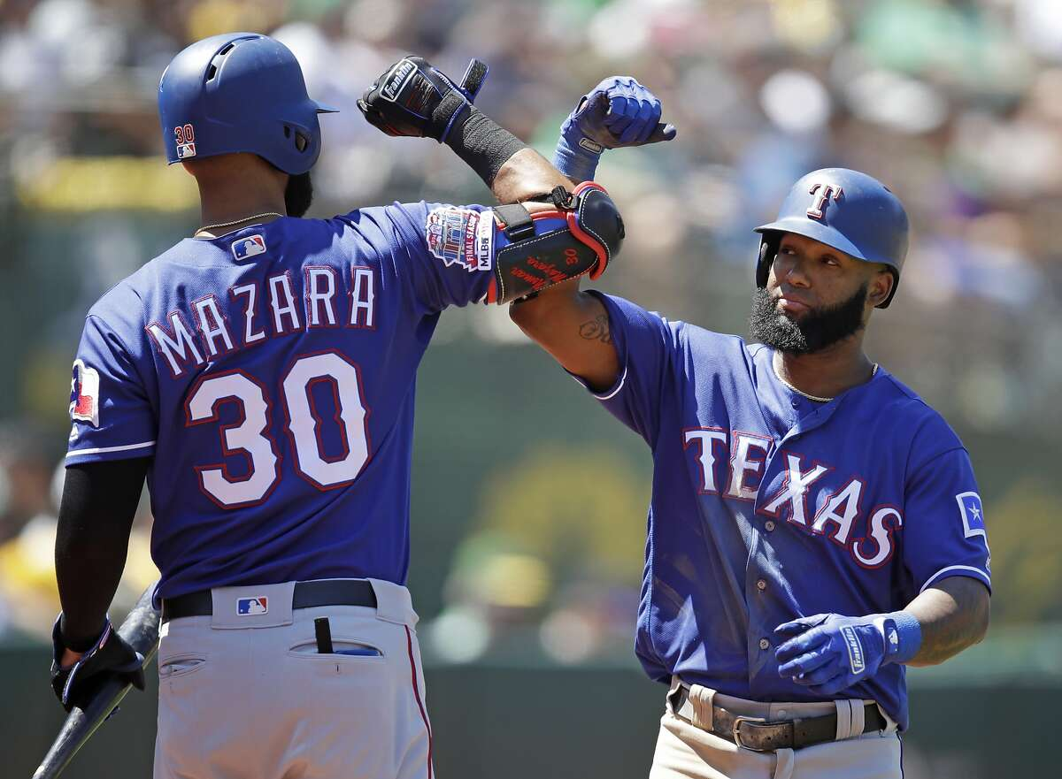 Texas Rangers' Danny Santana, right, celebrates with Nomar Mazara (30) after hitting a home run off Oakland Athletics' Mike Fiers in the sixth inning of a baseball game Sunday, July 28, 2019, in Oakland, Calif. (AP Photo/Ben Margot)