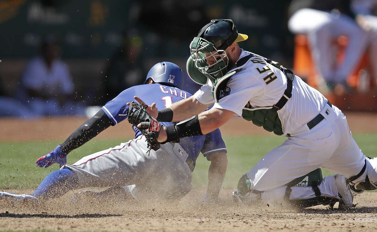 Texas Rangers' Shin-Soo Choo, left, is tagged out at home plate by Oakland Athletics catcher Chris Herrmann in the eighth inning of a baseball game Sunday, July 28, 2019, in Oakland, Calif. (AP Photo/Ben Margot)